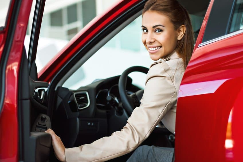 Glad kvinna i röd bil
