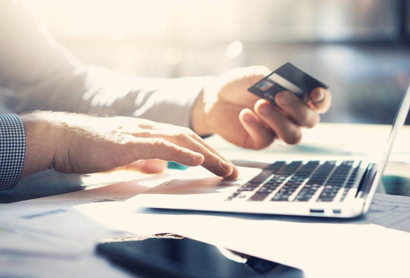 man sitter vid dator och betalar med kort