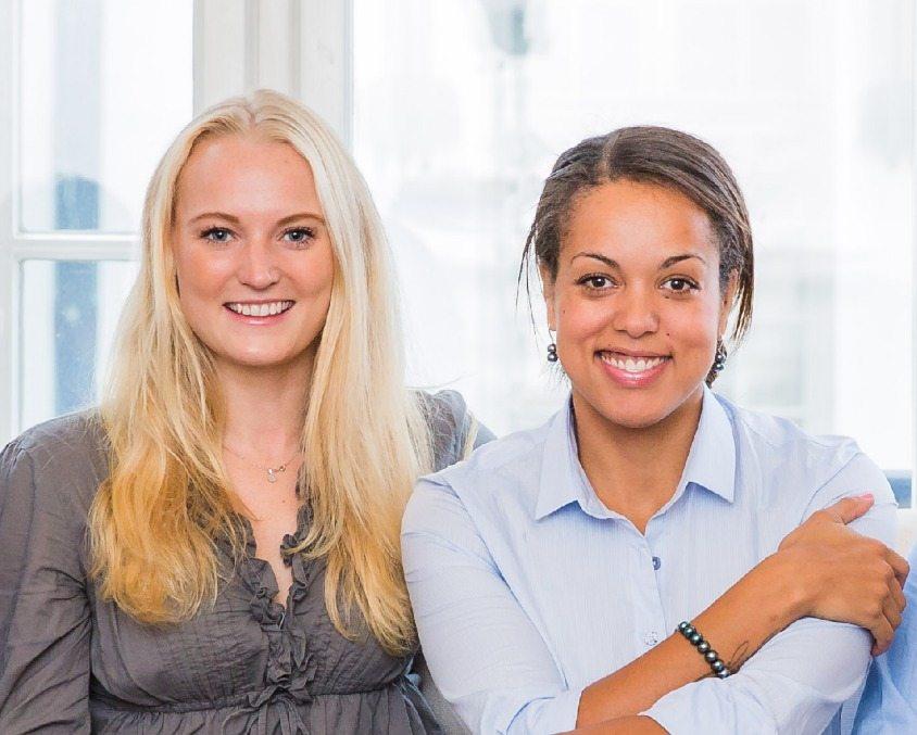 två kvinnor som ler in i kameran