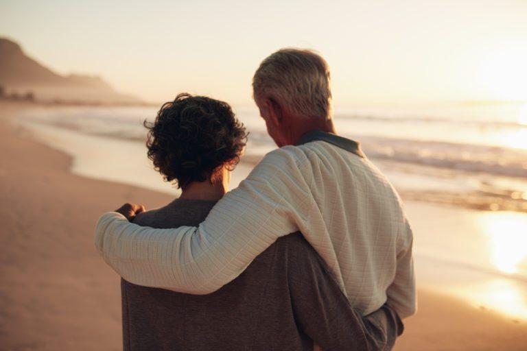 äldre par går längs stranden
