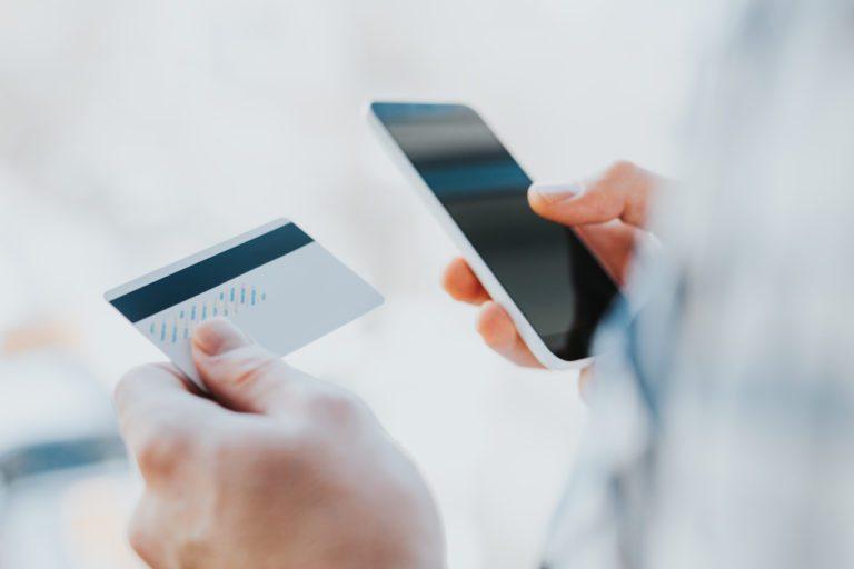 händer håller upp betalkort och mobiltelefon