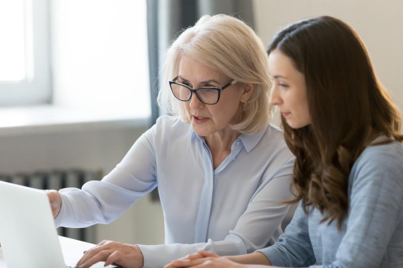 två kvinnor sitter framför datorn
