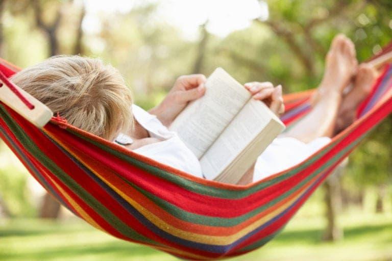 kvinna läser bok i hängmatta