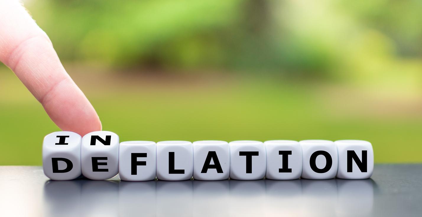 Hand visar upp tärningar som stavar ordet inflation